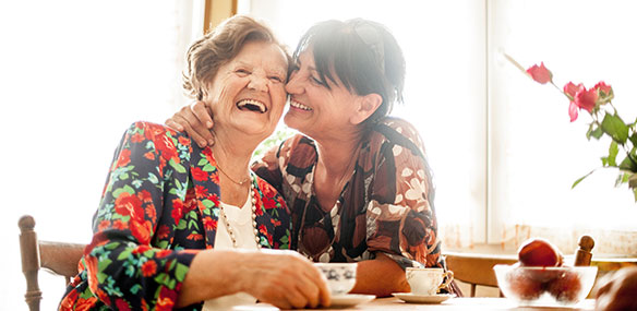 Daughter and elderly mother laughing