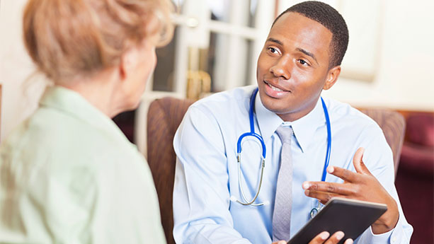 Male african-american doctor in discussion with white female patient