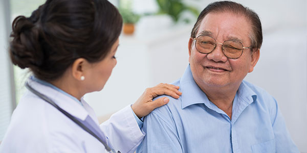 Asian doctor comforting senior asian male patient
