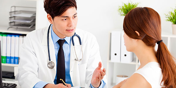 Asian doctor and young female patient in discussion