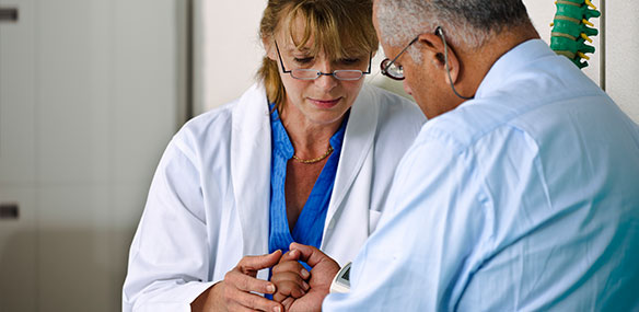 Doctor checking hand movement of male patient