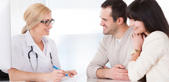 Happy couple in discussion with doctor