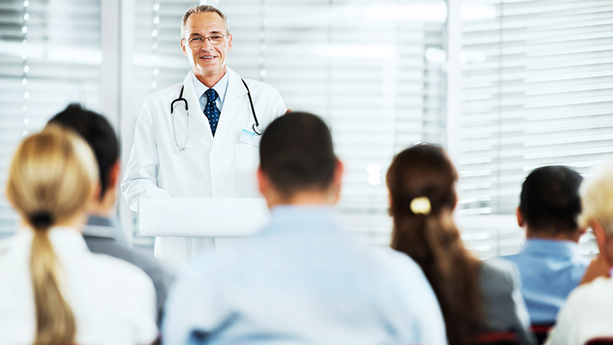 mature doctor talking to group