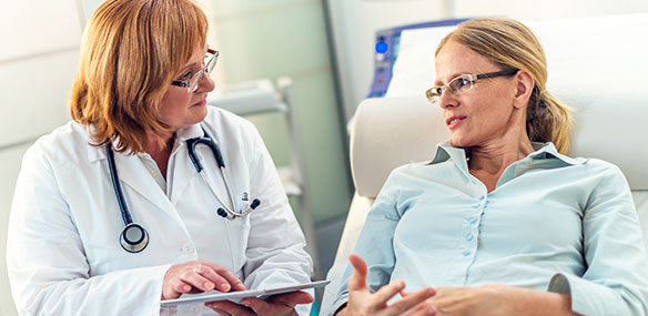 Mid adult woman discussing with female doctor