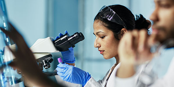 Researcher looking at vile near microscope.