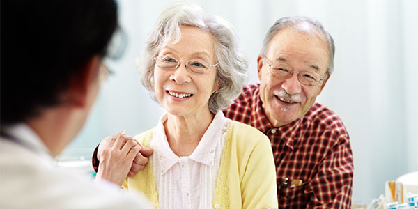 Senior asian couple talking to doctor