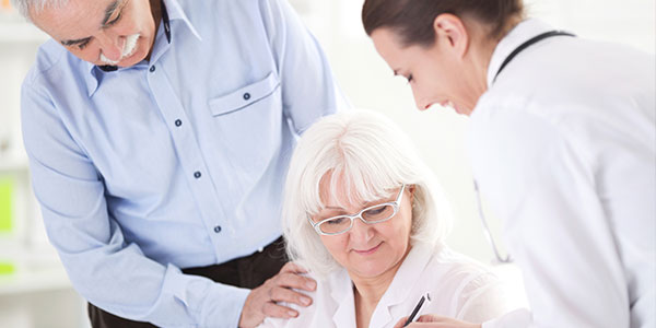 Senior couple filling out paperwork with doctor