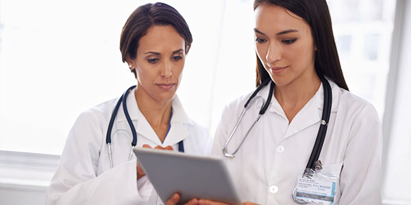 Two female doctors looking at digital tablet research