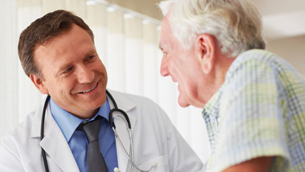 Male doctor in discussion at doctor's office with elderly male patient