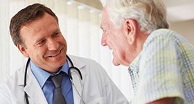 White male doctor with elderly male patient