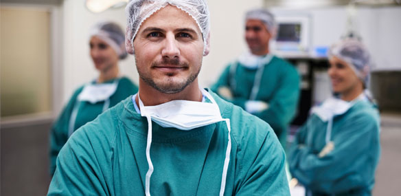 Male surgeon in forefront with surgical team in background