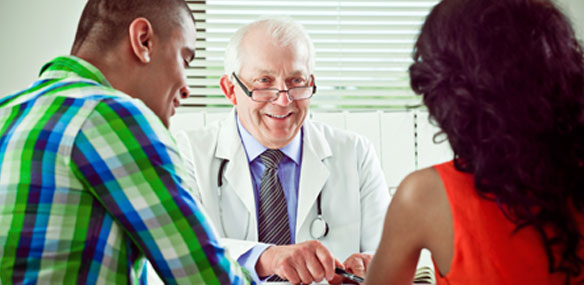 Young Hispanic couple consulting with doctor at doctor's office