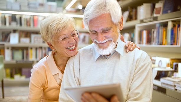 Caucasian senior couple using digital tablet in library