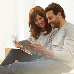 Couple sitting on floor in apartment looking at digital tablet