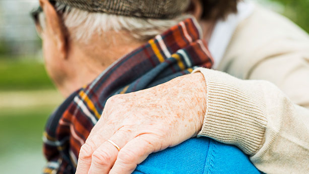 Older man with hand on shoulder
