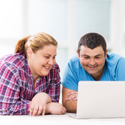 Overweight couple viewing laptop