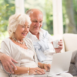 Elderly white couple working on laptop
