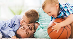 Dad laying on the ground with two sons and holding a basketball
