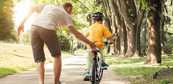 Father teaching young son to ride bike
