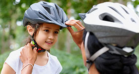 Mom adjusting little girl's helmet