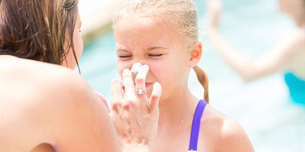 Mother          applying sunblock to daughter's face