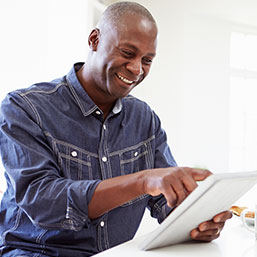 Man smiling while using mobile tablet