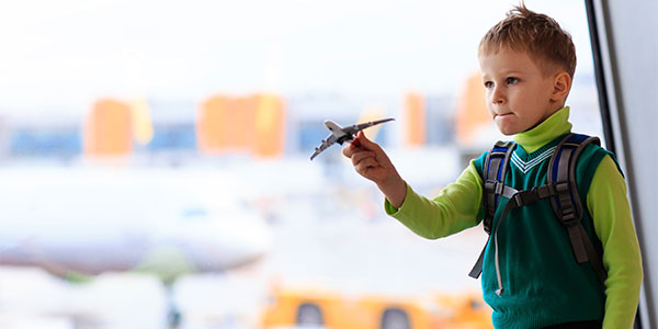 Little boy playing with toy airplane at airport