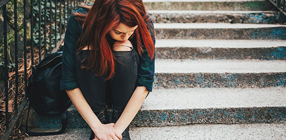 Teen girl sitting on steps with head down