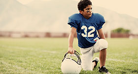 youth football player kneeling on field