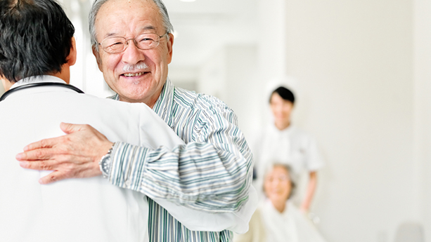 asian patient hugging doctor